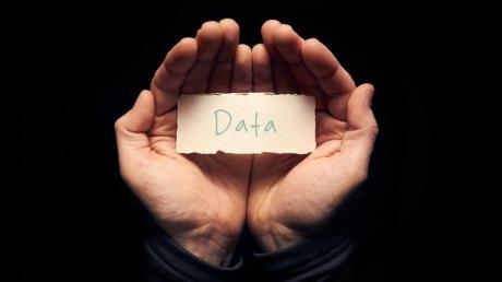 A man holding a card in cupped hands with a hand written message on it, Data.